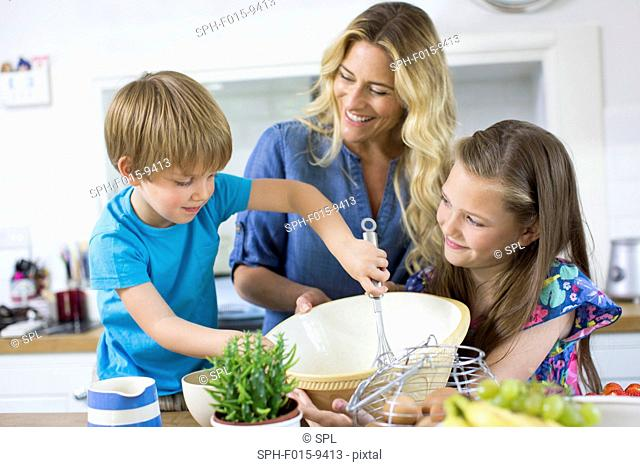 MODEL RELEASED. Mother and son and daughter cooking in the kitchen