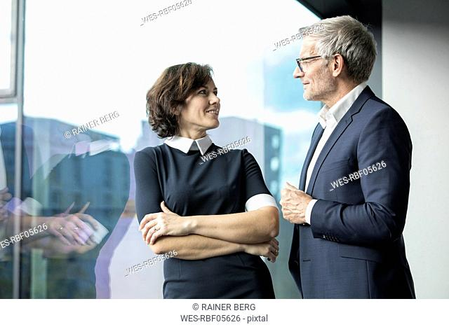 Smiling businessman and businesswoman talking at the window