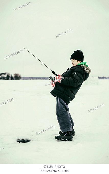 A young boy ice fishing and gets a bite while ice fishing at Wabamun Lake; Wabamun, Alberta, Canada