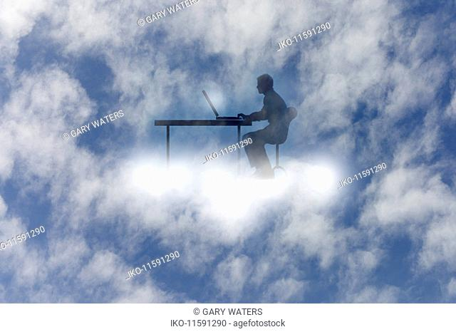 Man using laptop at desk cloud computing in the sky