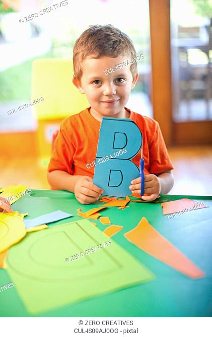 Portrait of boy with letter B at nursery school