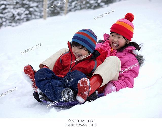 Laughing Japanese children sledding