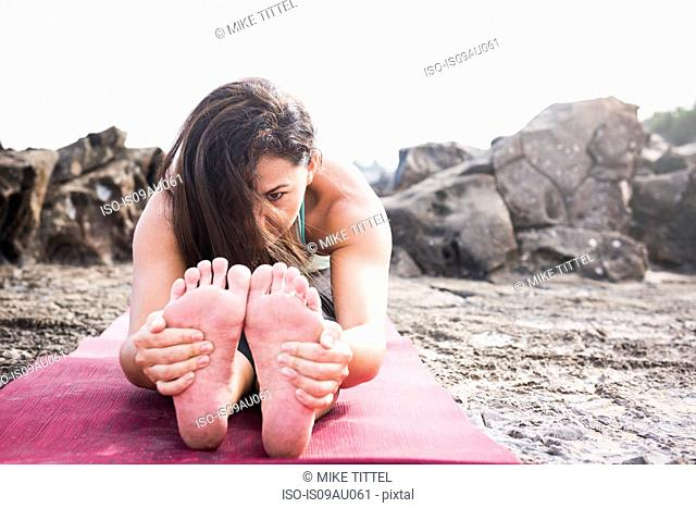 Woman holding her feet practicing yoga on beach
