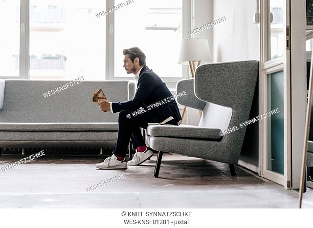Architect on couch holding architectural model
