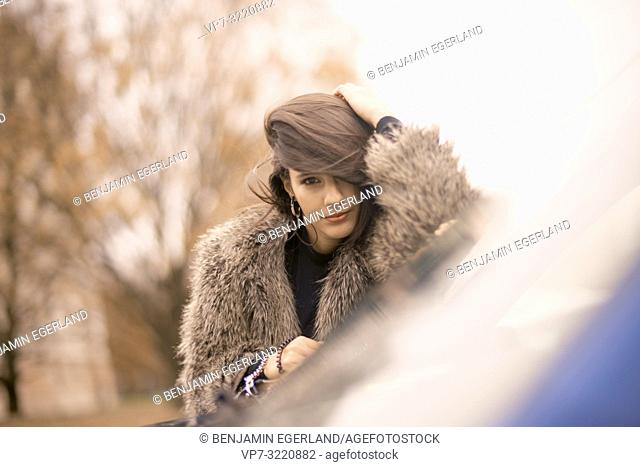 portrait of woman raking hairs, leaning on car window in city, autumn season, Munich, Germany