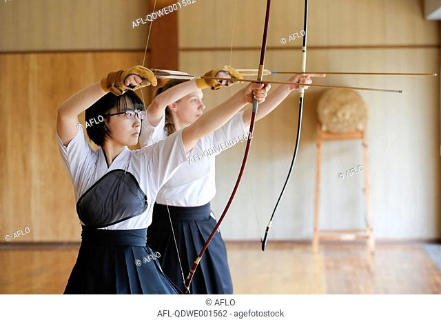 Multi-ethnic traditional Kyudo Japanese archery athletes practicing