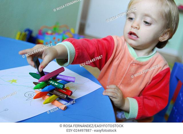 Baby girl drawing and making a little tower with colored pencils, Madrid, Spain
