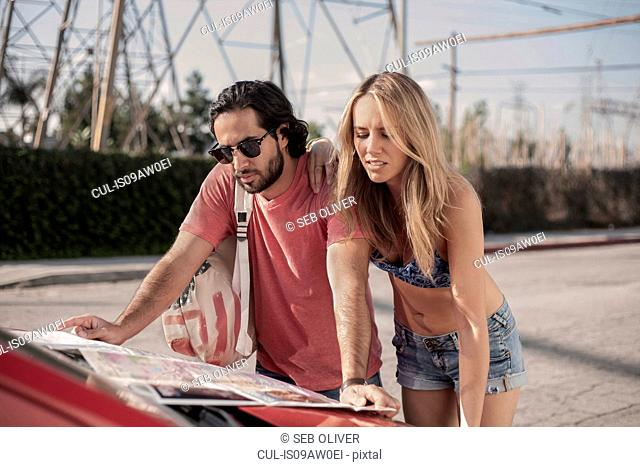 Young couple reading roadmap on car bonnet, Los Angeles, California, USA