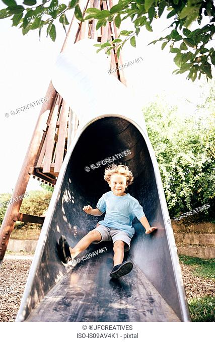 Boy sliding down playground slide looking at camera smiling, Ulm, Baden Wuerttemberg, Germany