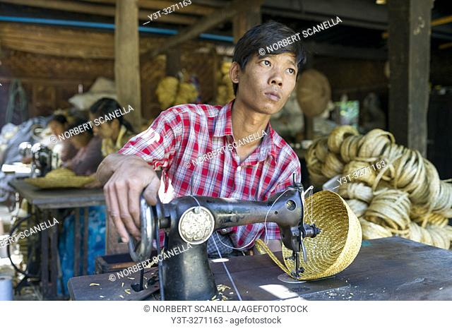 Myanmar (ex Birmanie). Sagaing, region of Mandalay. Rural village. Young man working at Manufacture of straw hats