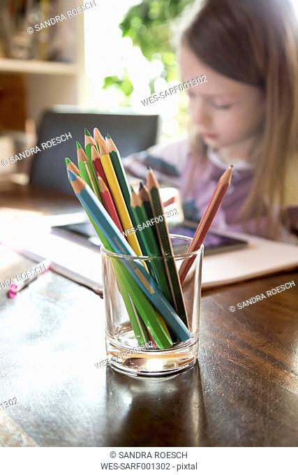Glass of coloured pencils