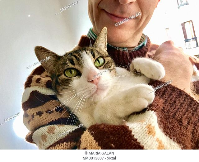 Man holding his tabby and white cat in arms. Close view