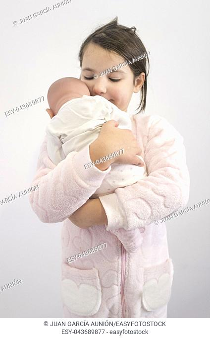 6 years little girl holding affectionately her reborn doll. Isolated over white