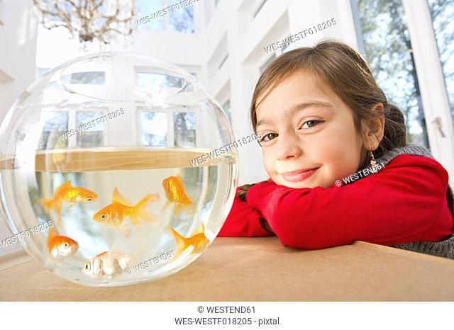 Germany, Bavaria, Grobenzell, Girl with goldfish bowl, smiling, portrait