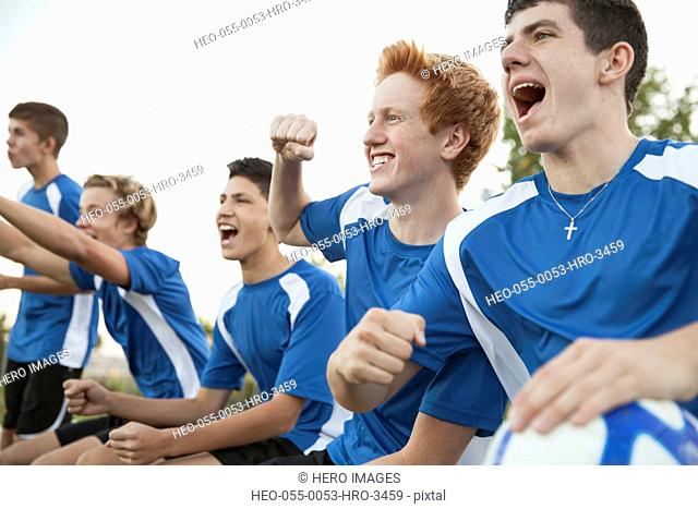 Soccer team cheering from bench