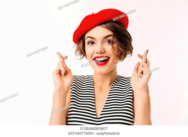 e00df2f9638 Portrait of a lovely woman wearing beret holding fingers crossed for good  luck isolated over white