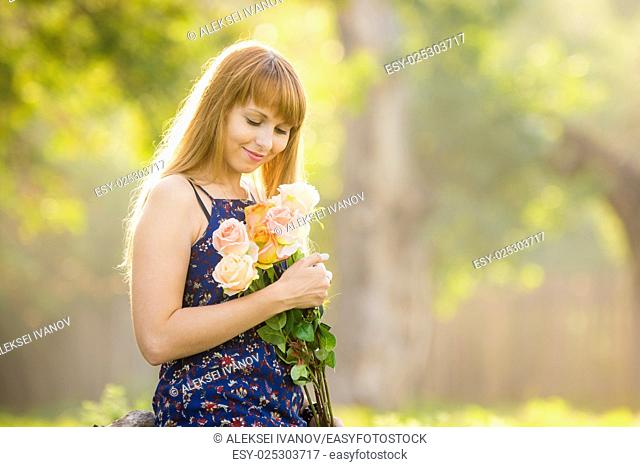 Beautiful young sexy girl looks at a bouquet of roses given to her standing against a background of green sunny blurred