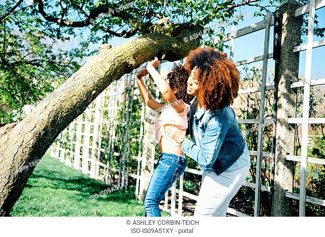 Side view of mother helping daughter to climb tree