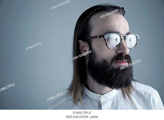 Portrait pensive brunette Caucasian young man with beard and eyeglasses looking away