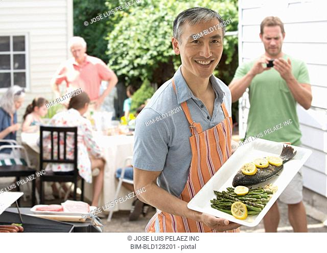 Chinese man holding platter of fish on patio