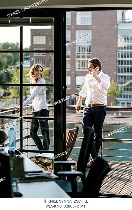 Businessman and woman standing on balcony, man making a phone call