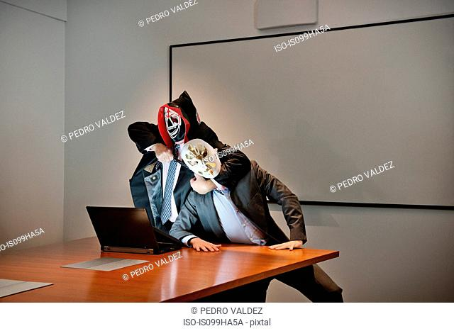 Businessmen in masks fighting over laptop