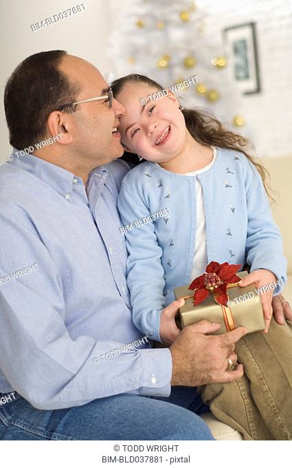 Hispanic grandfather giving gift to granddaughter