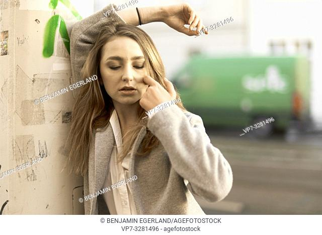 young thoughtful woman with closed eyes outdoors at street, green, in Cottbus, Brandenburg, Germany