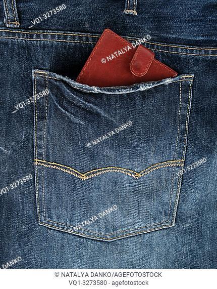 Brown leather wallet in the back pocket of blue jeans, full frame