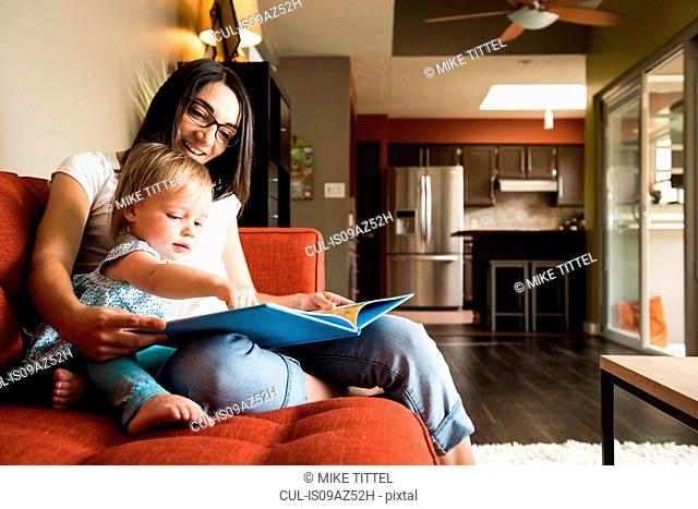 Mother teaching daughter to read book on sofa