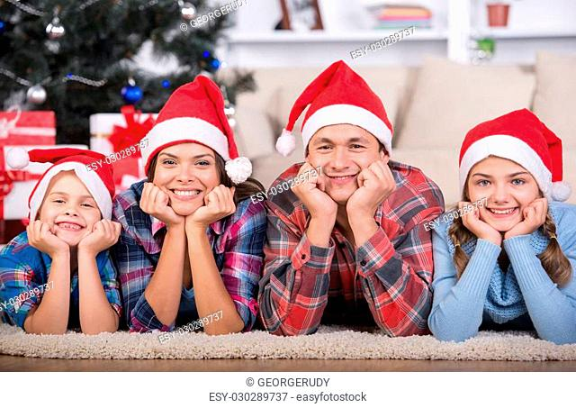 Portrait of friendly family are looking at camera on Christmas evening. Christmas Tree. Santa Hat