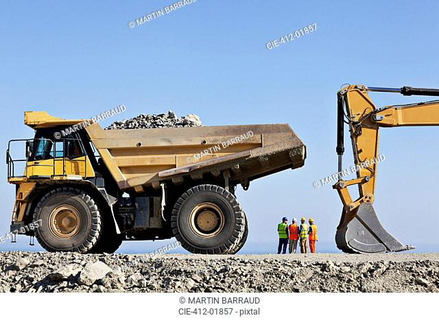 Workers and machinery in quarry
