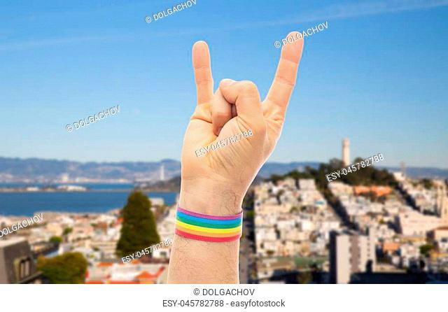 lgbt, same- relationships and homosexual concept - close up of male hand wearing gay pride awareness wristband showing rock or hand-horns sign over san...