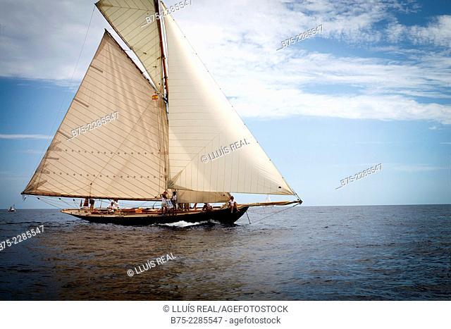 Vintage sailboat sailing with 2 approaches, wholesale and retail, spanker sail and scandalous in the Mediterranean Sea on a calm, sunny day