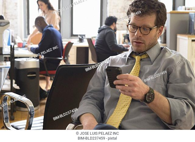 Businessman texting on cell phone in office