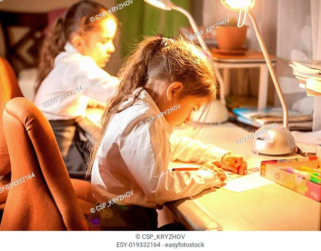 Little schoolgirl sitting behind table and drawing
