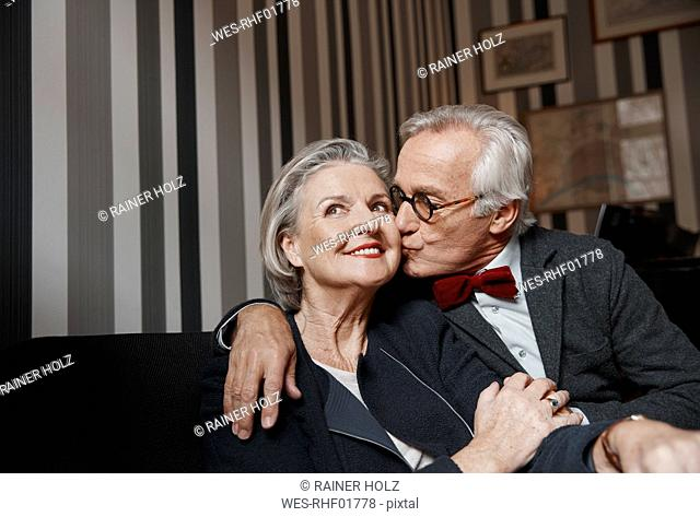 Senior man kissing wife on couch