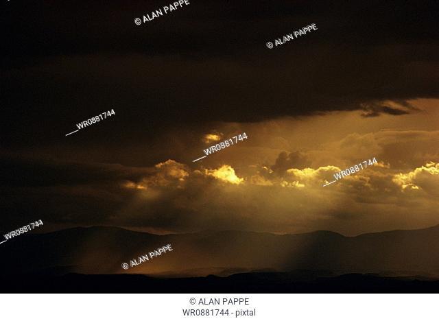 View of sunlight through dark clouds