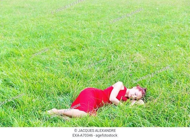 Woman with red dress on meadow