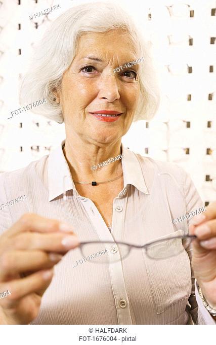 Portrait of smiling senior woman holding eyeglasses at store