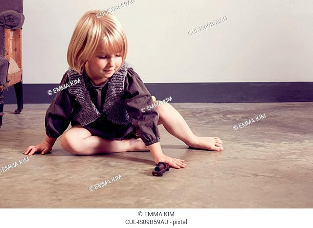 Girl playing on floor with old wooden toy locomotive