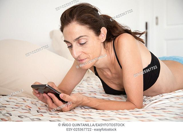 brunette smiling woman wearing black bra lying on the bed using mobile phone touching screen
