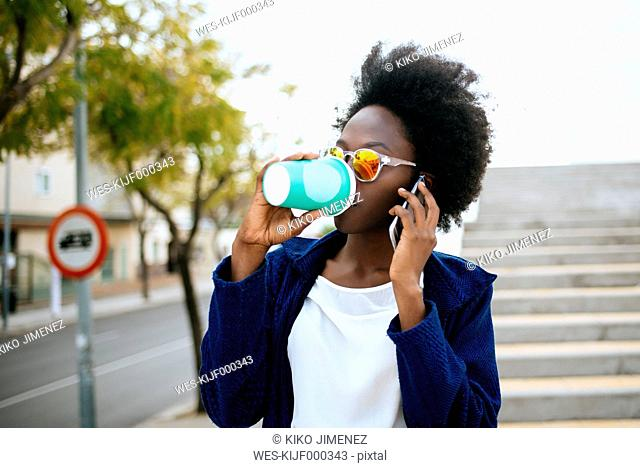 Young woman with coffee to go telephoning with smartphone