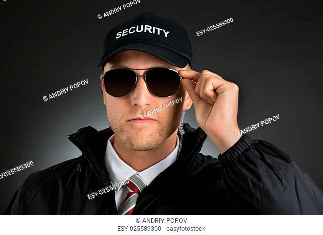 Portrait Of Security Guard Wearing Sun Glasses Over Black Background