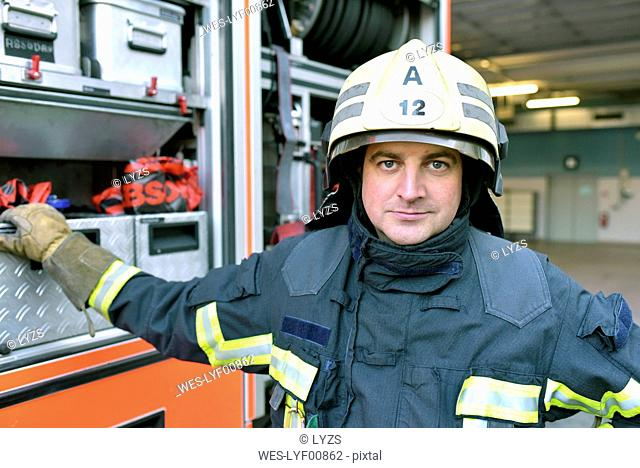 Portrait of confident firefighter in front of fire engine