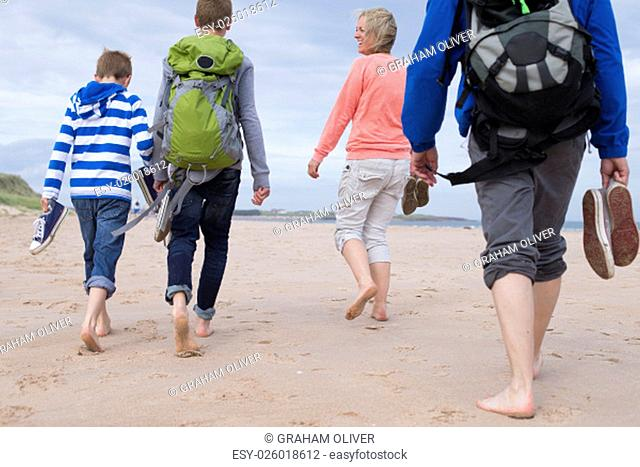 Family of four walking along the beach barefoot. They are wearing warm casual clothing