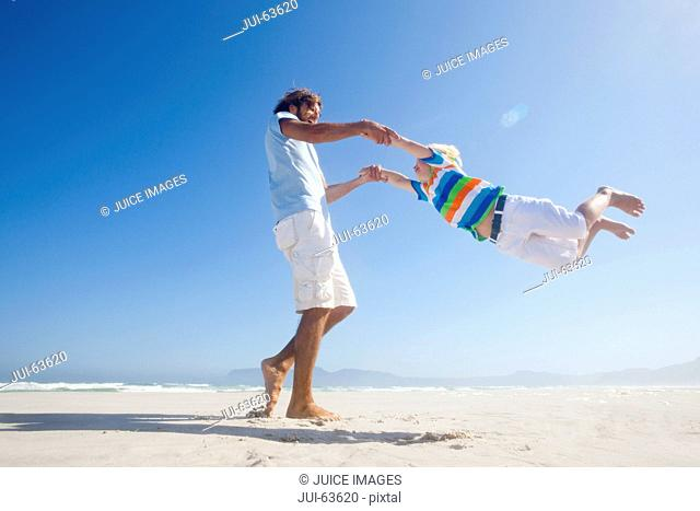 Smiling Father swinging son around playfully on sunny beach