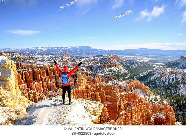 Young woman with outstretched arms and a view of the amphitheatre, bizarre snowy rocky landscape with Hoodoos in winter, Rim Trail, Bryce Canyon National Park