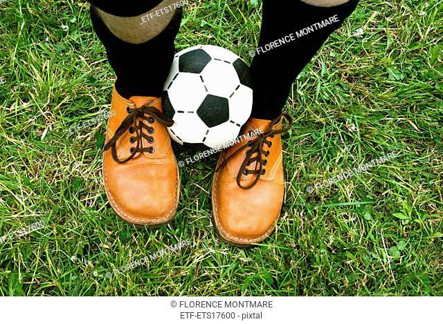 A football between two feet