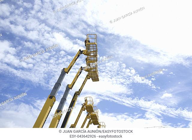 Telescopic Booms. Some platforms lifted over blue sky